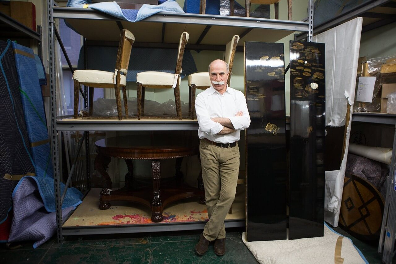Miguel Saco, in his East 18th Street studio, standing next to two Jean Dunand panels from the 1930s. Photo: Cassandra Giraldo for the Wall Street Journal